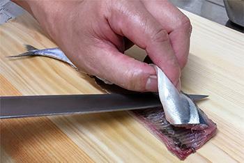 秋刀魚(さんま)を骨に沿って切ります。